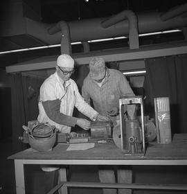 Welding, Terrace, 1968; two men standing at a table looking at an item that was welded, welding e...