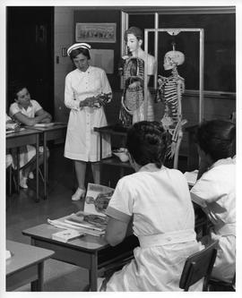 Nursing teacher and students looking at anatomical dummy and skeleton, Prince George, BC (ca. 196...