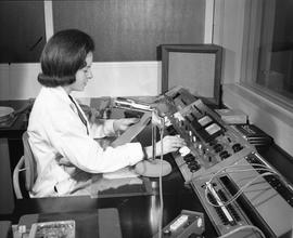 BCIT Broadcast and Television, 1964; woman reading a script in a radio recording booth