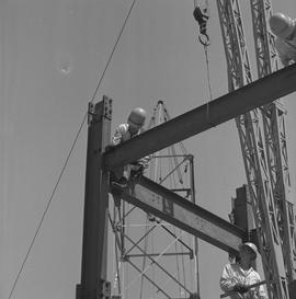 Structural steel, 1968; worker tightening bolts on the corner of a structure; worker watching fro...