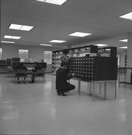 BCIT Burnaby campus library ; two people using a card catalogue ; people sitting at desks [1 of 2]