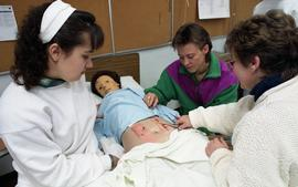 General Nursing, students and nurse examining dummy patient in a bed [5 of 5 photographs]