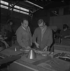 Sheet metal, 1968; instructor watching a student using scissors to cut sheet metal ; other studen...
