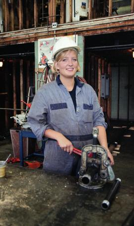 BCIT Women in Trades; plumbing, woman with pipe (cutting?) machine, September 1, 1995 [3 of 9 pho...