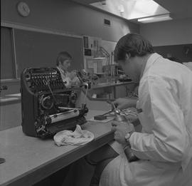 Office Machine Mechanic, 1968; man repairing the letter pieces of a typewriter ; student working ...