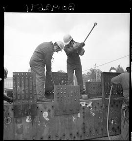 B.C. Vocational School image of Boilermaker students hammering metal plates with sledgehammers