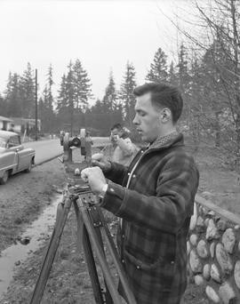 Survey, 1964; a man using a surveying level and another man holding a measuring tape [1 of 2]