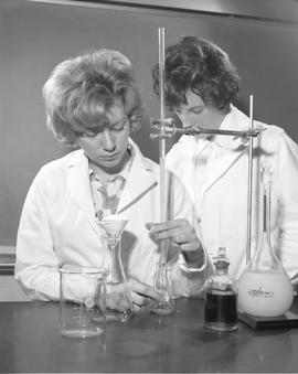 Medical Lab; a woman in a lab coat standardizing solutions, a woman in a lab coat standing next t...