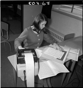 B.C. Vocational School; Commercial Program student in a classroom using an adding machine at a de...