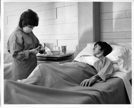 BCVS Nursing student, wearing mask, cutting something with scissors near patient, 1968