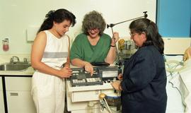 C/Care (students in action), 1993, students with medical machine [1 of 3 photographs]