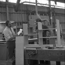 Carpentry apprenticeship contest, Burnaby campus, 1978 ; apprentice measuring their shelf while a...