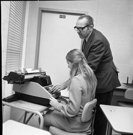 BC Vocational School Commercial Program; instructor showing a student how to use a typewriter