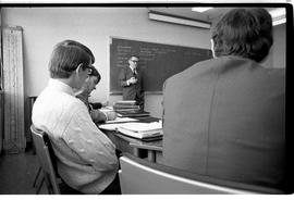 BCIT Business Management images of male students sitting at desks with instructor standing at a b...