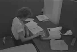 Pacific Vocational Institution ; student sitting at a desk reading a textbook and using a calculator
