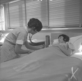 Practical nursing, Prince George, 1968; student checking a patient's blood pressure [1 of 2]