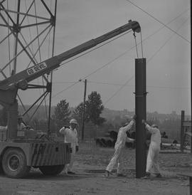 Structural steel, 1968; workers using a crane to place a large piece of steel into the ground [1 ...