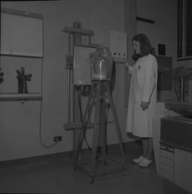Medical radiography, 1968; woman in a lab coat standing next to a manikin torso in front of an x-...