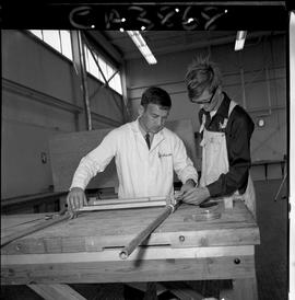 B.C. Vocational School; inside the Carpentry Trades shop instructor and student measuring cabinet...