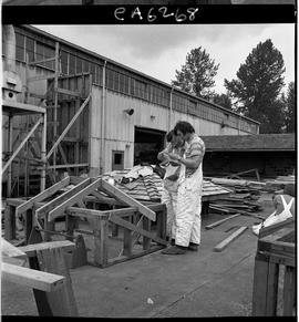 B.C. Vocational School; two Carpentry Trades students reading building plans in the yard outside ...