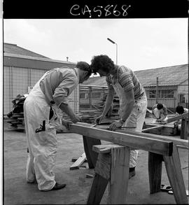 B.C. Vocational School; two Carpentry Trades students measuring two-by-fours that are sitting on ...