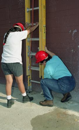 Pre-trade Aboriginal women; students wearing hard hats and holding up a ladder [2 of 6 photographs]