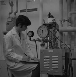 Mechanical technology, 1968; man in a lab coat looking at pressure gauges and writing notes