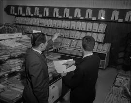 Business Management; a men's wear department ; one man holding a paper and another man pointing a...