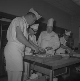 Tow boat cook course; instructor talking to two students chopping potatoes; student holding celer...
