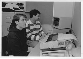Broadcast Communication 1980s(?); two male students in an office, one student using a computer an...