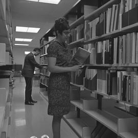 BCIT Burnaby campus library ; two people standing in an aisle looking at books