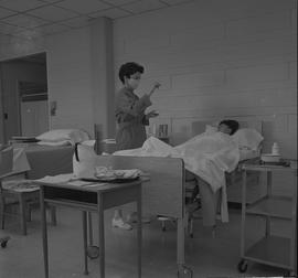 Practical nursing, Prince George, 1968; nurse wearing a face mask standing next to a patient's bed