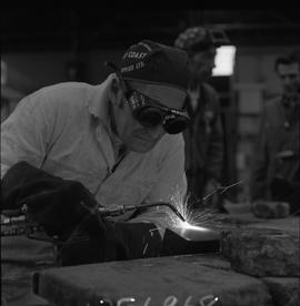 Welding, 1968; man wearing protective goggles and gloves welding ; people working in background [...