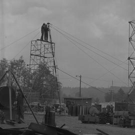 Structural steel, 1971; two men standing at the top of scaffolding holding onto a tall pole; peop...