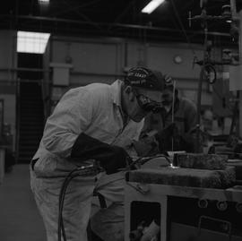 Welding, 1968; man wearing protective goggles and gloves welding ; man working in background [1 o...