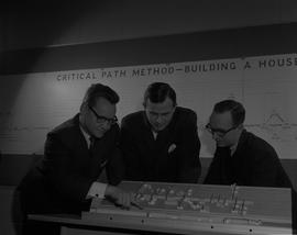 Business Management; three men looking at a miniature model of a store layout [2 of 2]