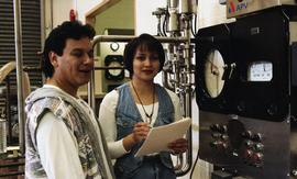 Male and female First Nations students standing near a milk pump pasteurizing equipment [2 of 4 p...