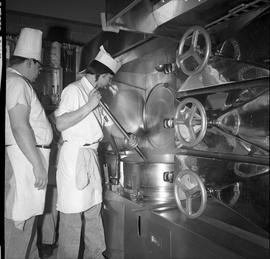 BC Vocational School Cook Training Course ; student stirring food in a large industrial pot ; stu...
