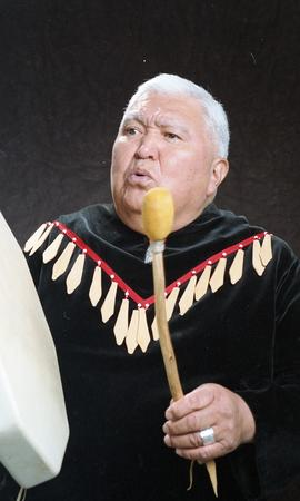 Bob George, First Nations elder, in First Nations garment playing an instrument [20 of 36 photogr...