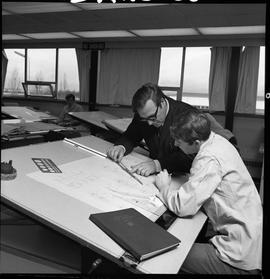 BC Vocational School drafting course ; instructor showing a student something on a ruler ; studen...