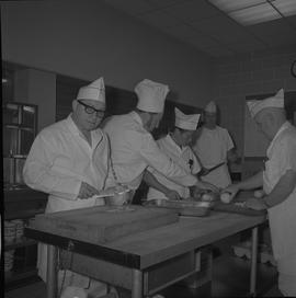 Tow boat cook course; students chopping vegetables, one student looking at the camera