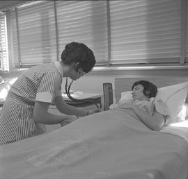 Practical nursing, Prince George, 1968; student checking a patient's blood pressure [2 of 2]