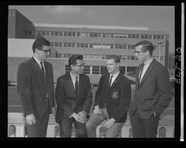 Four men (students) in suits, one with the BCIT crest on his jacket pocket, BCIT Electronics Council