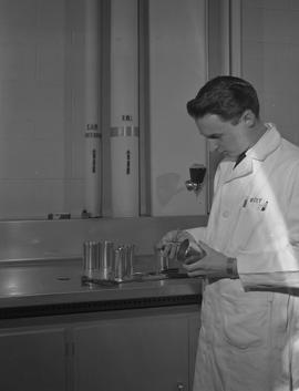 Food Processing Technology, 1966; man wearing a lab coat holding lab testing equipment, more equi...