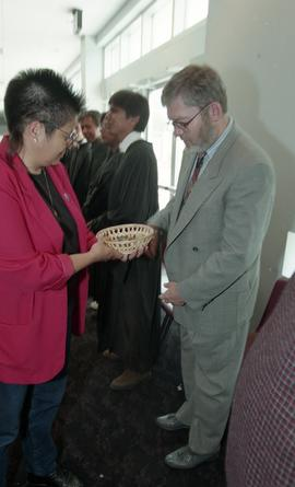 First Nations (?) woman presenting a wooden bowl filled with stones to staff member [1 of 3 photo...