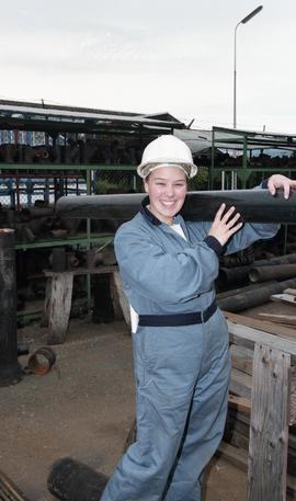 BCIT women in trades; plumbing, students in uniforms and hard hats carrying piping material [13 o...