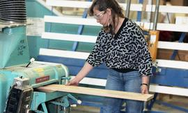 "BCIT Women in Trades Training; carpentry, woman with eye protection, feeding wood into a ""Po..."
