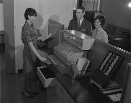 Hotel Motel, 1964; a man and woman standing at a staged hotel reception desk, a woman at the desk...