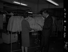 Business Management, 1964; a man and a woman in front of a clothing rack examining a coat