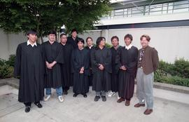 First Nations graduates standing outside in graduation robes with instructor (?) [1 of 5 photogra...